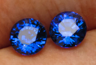 This matche pair of carat sized blue sapphires exhibit off-axis refraction also known as extinction.  The dark areas move as the gem moves partially defilning the positive areas of scintillation