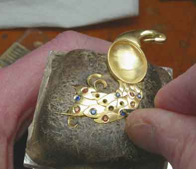 Setting the gems: Once the feathers have been dapped out and soldered together and the cast body has been finished and soldered to the tail, gem setting can begin, the method is known as thread and bead setting.Peacock Pendant: Micro view, all gems set.